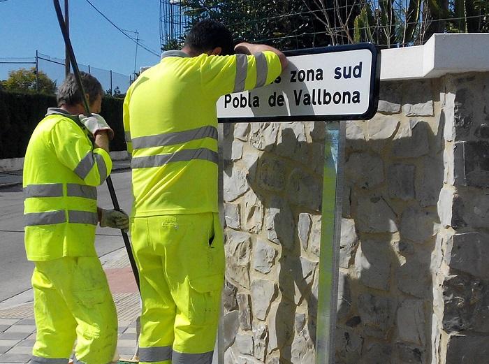 Dos operarios municipales colocan las nuevas señales informativas.