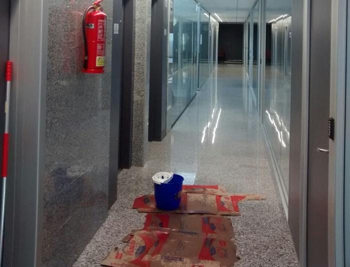 Pasillo de la planta superior del edificio multiusos de Llíria con cubos y cartones, esta mañana.