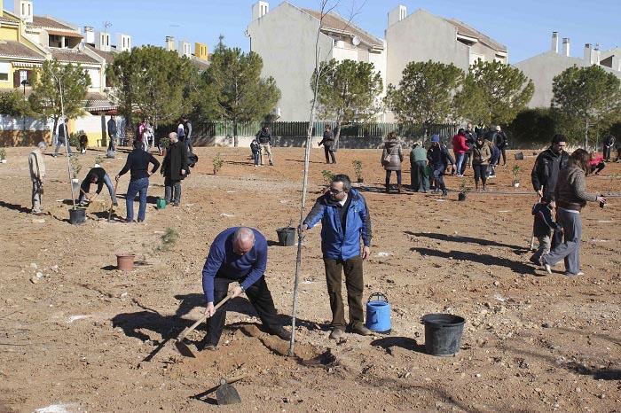Vecinos trabajando en una de las parcelas de la urbanización Reva de Riba-roja de Túria.