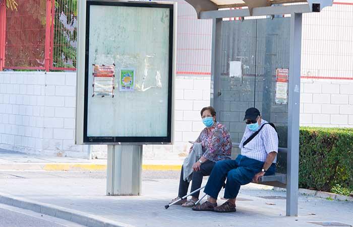Señor y señora en parada de autobus de Llíria con mascarilla